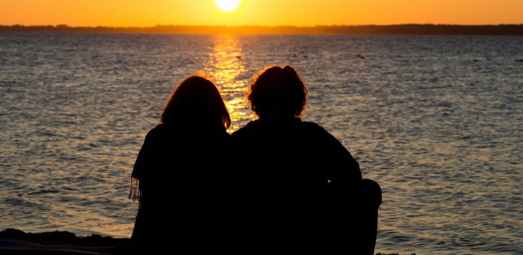 Zwei Pfadis sitzen vor Sonnenuntergang am Meer