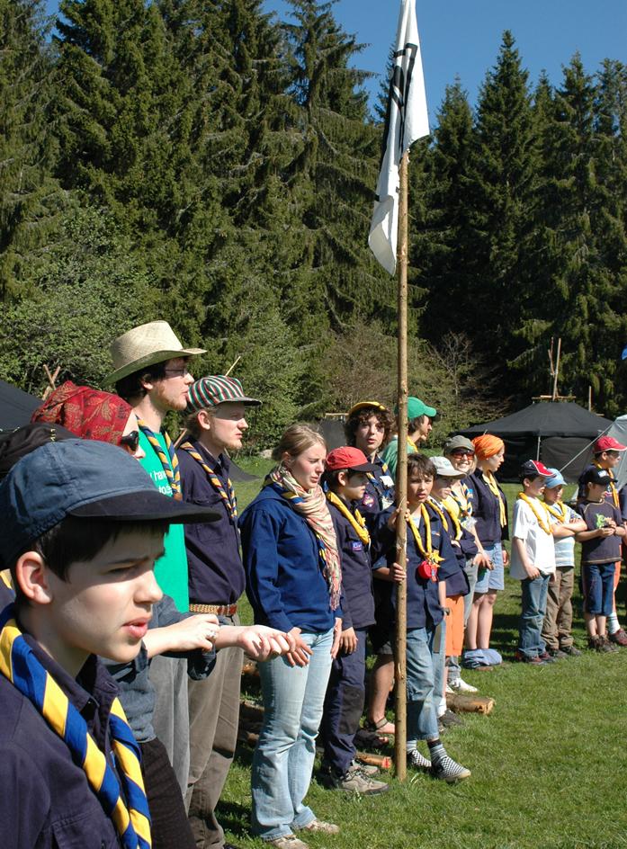 Pfadfinderinnen und Pfadfinder stehen in großem Kreis und halten ihre Stammesfahne