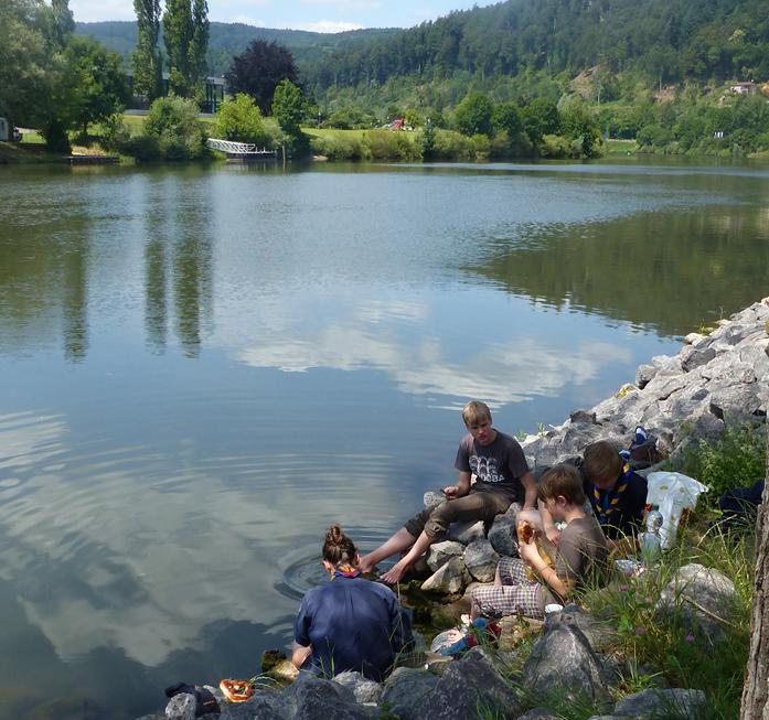 Eine Pfadfinder-Sippe frühstückt auf Fahrt am Flussufer